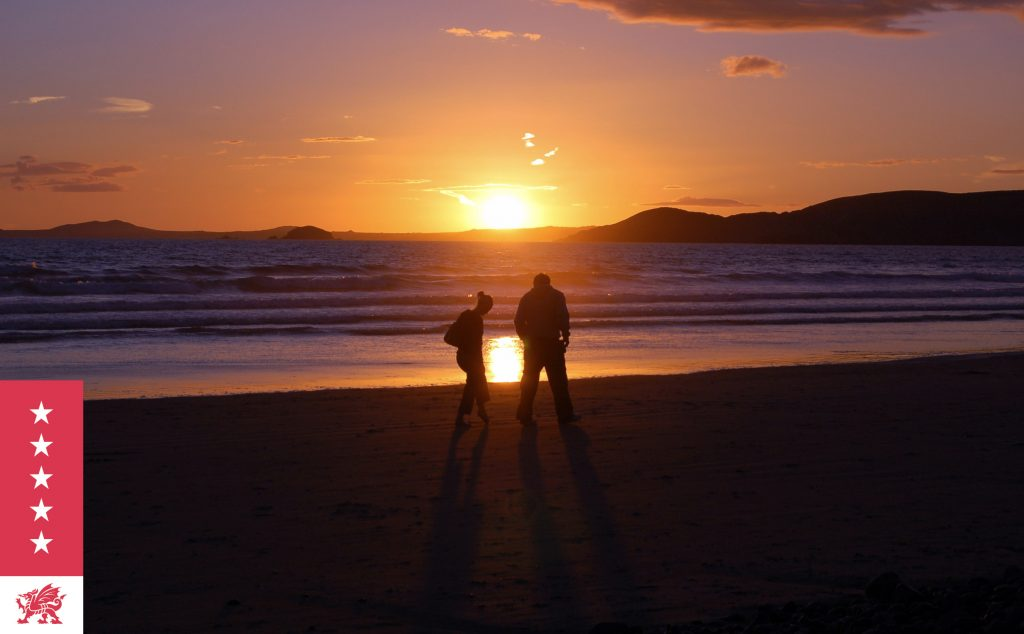 Couple taking a romantic sunset walk along the beach